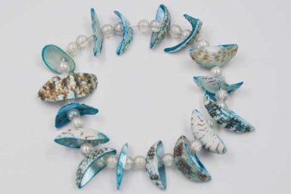 Elastisches Armband mit blauen Muscheln und weissen Acryl-Kugeln